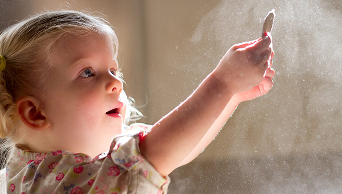 Young girl captivated by dust particles floating in the sunlight